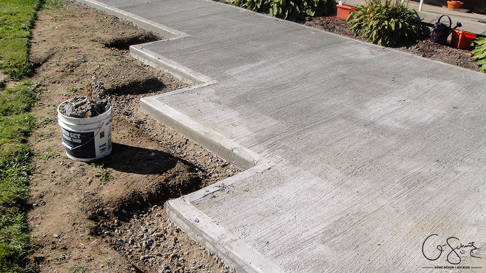 Our project walkway is almost complete now that the DIY concrete is set. Check out the pictures of how it looks currently and read my pros and cons of going with a DIY walkway versus professional concrete.