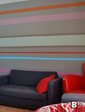 Our striped accent wall helps bring all the crazy and wild colours we used throughout the house into one cohesive location!