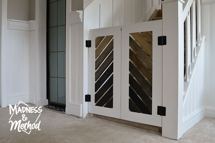 This rustic saloon style DIY baby gate is the perfect solution to prevent baby from going up the stairs when you don't have a lot of door swing space.