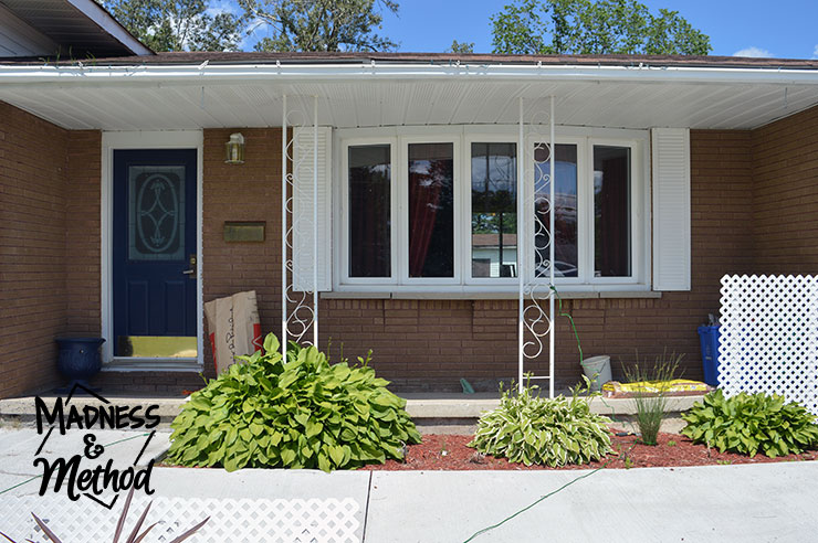 Front house view with concrete front porch and bay window