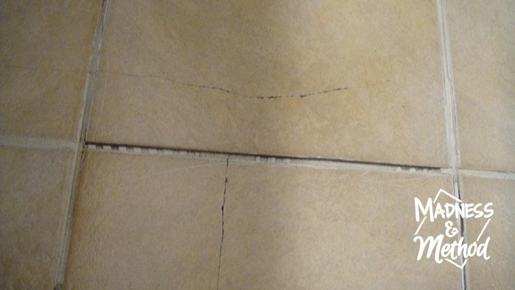 closeup of cracked tile with grout removed
