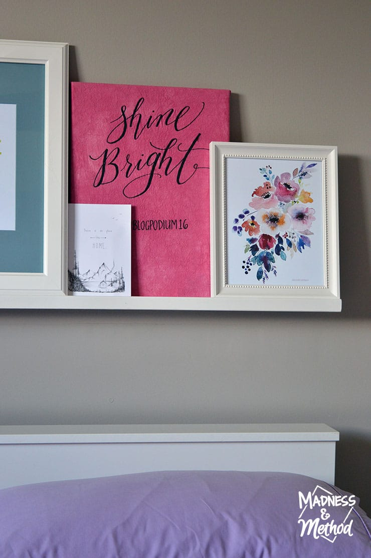 Bright coloured prints on a photo ledge behind a bed
