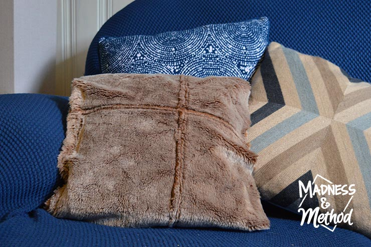 beige faux fur pillow on a blue couch