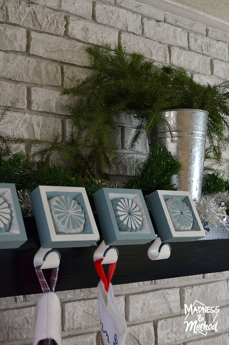 simple silver and green holiday mantel with greenery