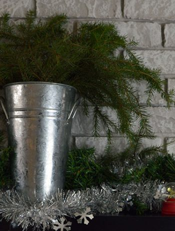 bucket with greenery on holiday mantel