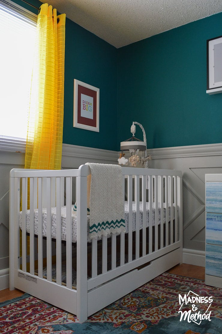 dark teal walls and white crib