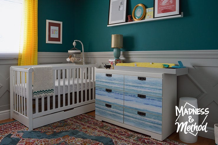dark teal nursery with white furniture