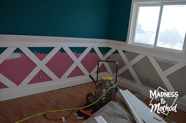 placing flat trim panels to make diamond wainscoting