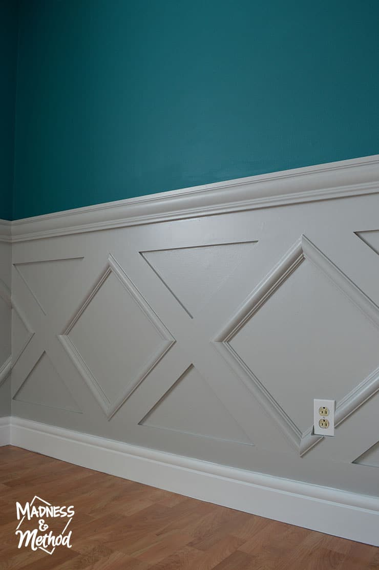 gray wainscoting and deep teal walls