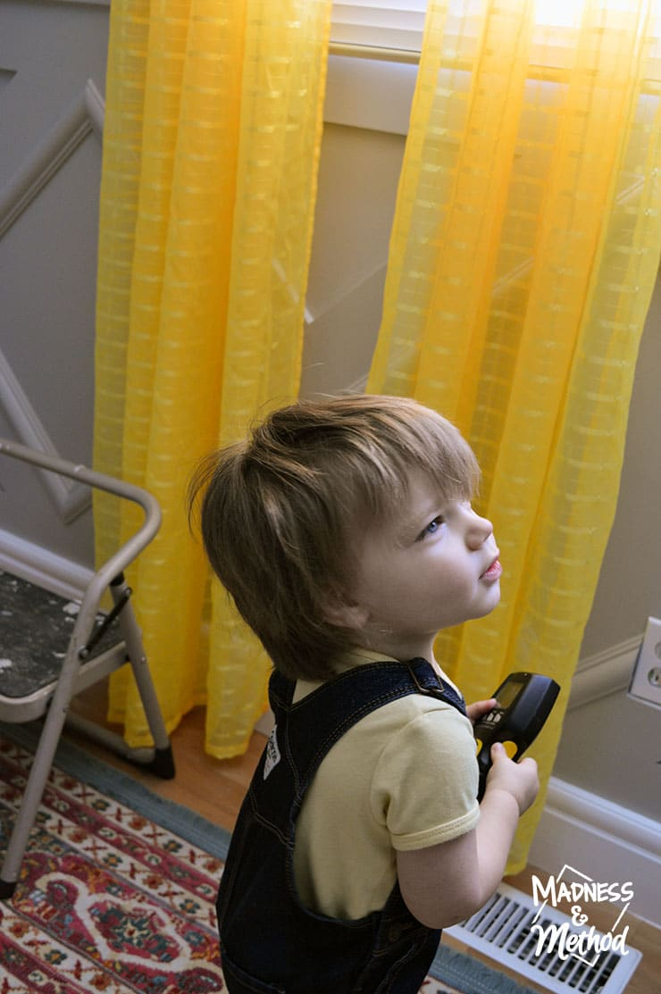 baby helping install curtains