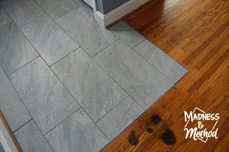 grey tiles next to wood floors