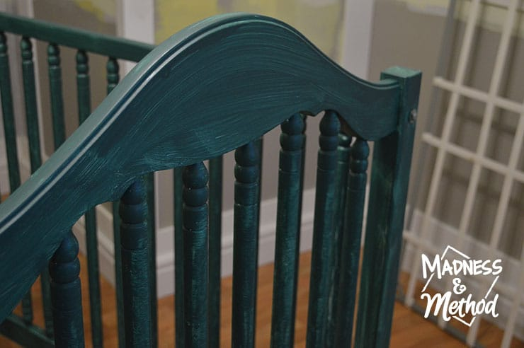 first coat of dark teal paint on crib
