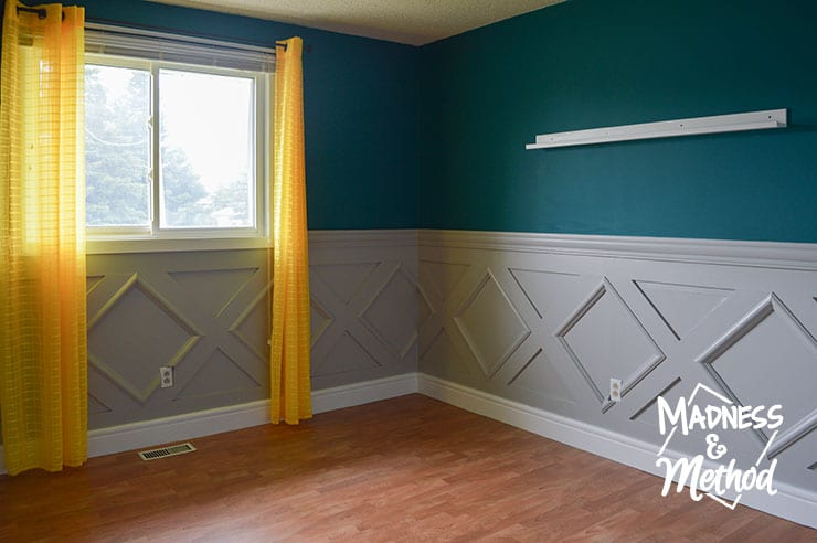 teal bedroom with gray wainsoting