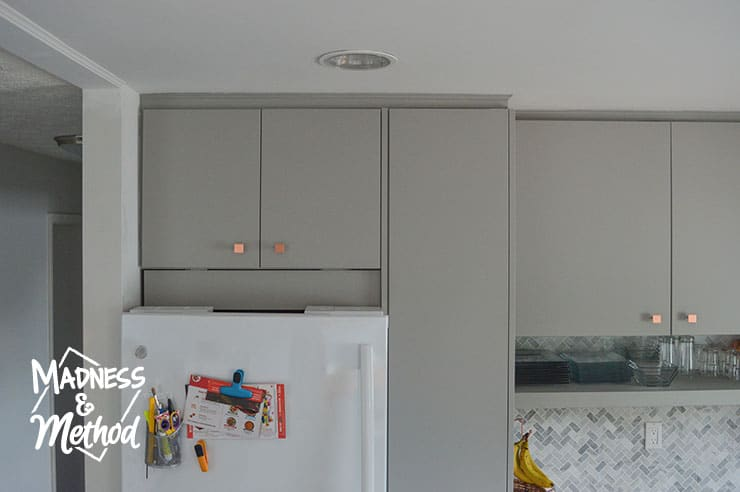 small removable panel above fridge